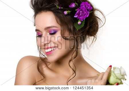 Portrait of young beautiful female holding white rose with violet cloves in her hair. Bright spring or summer modern fashion make up. Pink lips and smokey eyes. Skin care or natural cosmetics concept