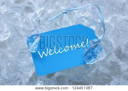 Light Blue Label With Blue Ribbon On White Transparent Curshed Ice Cubes As Background. English Text Welcome For Cool Greetings.Close Up Or Macro View.