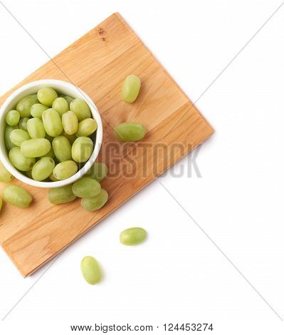 White table grapes in a ceramic bowl over the serving wooden board, composition isolated over the white background, framed as a copyspace background composition