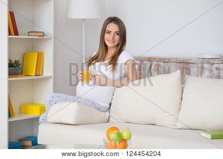 Beautiful pregnant woman looking at camera and smiling sitting on a couch. The happiest time for every woman. Fruit and orange juice in the hands of a pregnant woman.