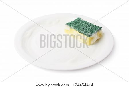 Foam covered dish washing kitchen sponge over the surface of the white ceramic plate, composition isolated over the white background
