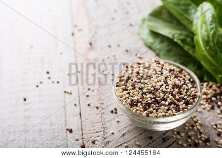 Pile of mixed raw quinoa in glass bowls and fresh organic sorrel on white rustic wooden background. Healthy and gluten free food. Copy space.