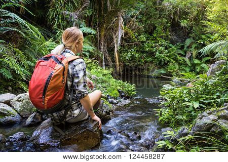 Young woman hiker sitting on rocks in stream