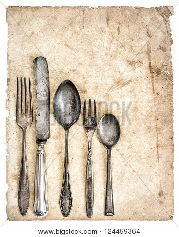 Antique cutlery and old cook book page. Retro kitchen utensils knife fork and spoons