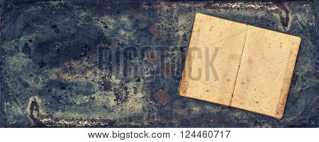 Open antique book on rustic metal texture background. Vintage style toned banner