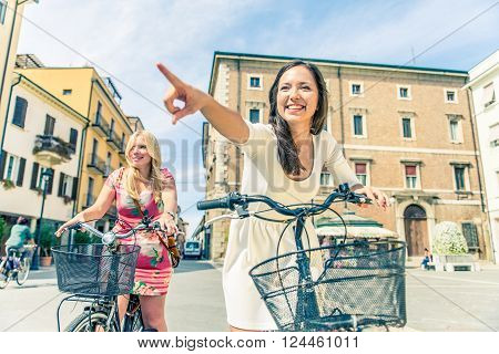 Happy couple riding bikes in the city - Two girlfriends on bikes talking and laughing - Best friends spending time together on vacation