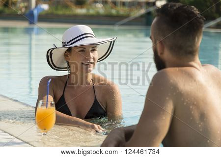 Young couple in a swimming pool holding to the edge having a conversation ejoying the sun