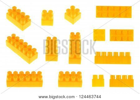 Set of plastic orange toy construction block bricks in multiple foreshortenings, isolated over the white background