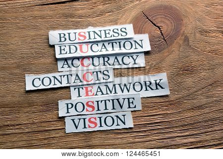 Success  acronym in business concept, words on cut paper on wooden background