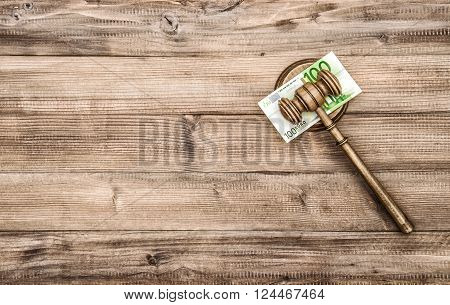 Judges Gavel with euro banknotes. Auctioneer hammer on wooden background