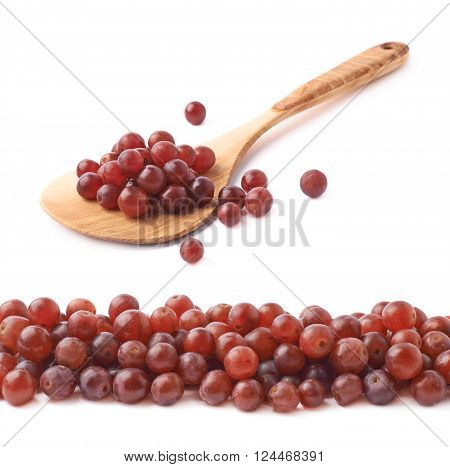 Wooden spoon ladle covered with multiple dark red grapes with the line of grapes in front of it, composition isolated over the white background