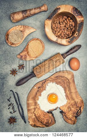 Baking utensils and ingredients on kitchen table. Eggs flour sugar almond vanilla. Vintage style toned picture