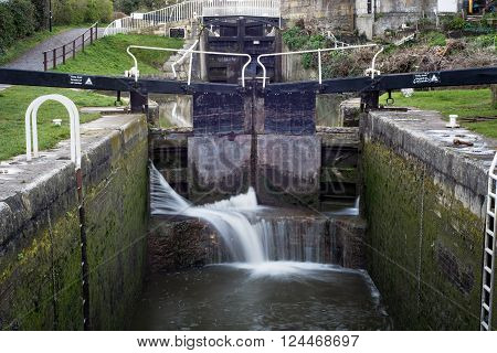Widcombe locks on Kennet and Avon Canal. Lock with water escaping at high pressure through gaps, spilling onto cill