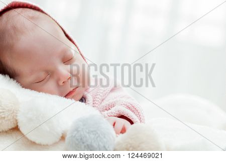 Newborn baby sleeping on white fur blanket. White background.