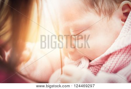 Little newborn baby in her mother arms. Close-up