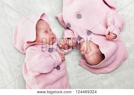 Newborn twins sisters sleeping on white fur, wearing cute pink sweaters