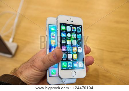 PARIS FRANCE - APR 4 2016: Man comparing iPhone 6s and the new Apple iPhone SE during the sales launch of the latest Apple Inc. smartphone and iPad Pro at the Apple store in Paris France