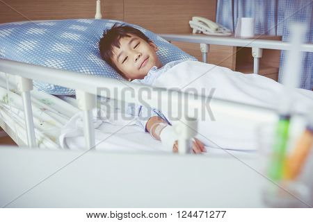 Illness asian boy lying on sickbed in hospital with infusion pump intravenous IV drip. Child smile and look at camera. Shallow depth of field child in focus, saline intravenous out of focus. Vintage.