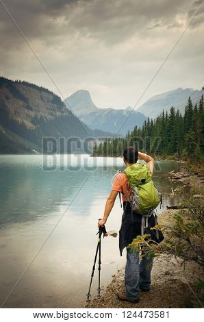 Hiker rest at lake side in a rainy day with mountain forest and cloud.