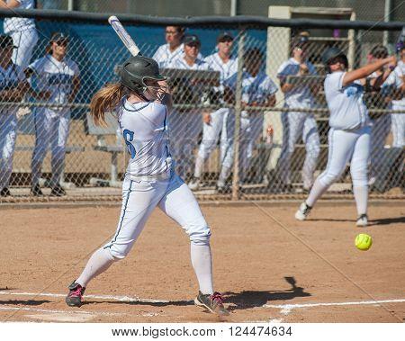 High school softball player hitting a ground ball.