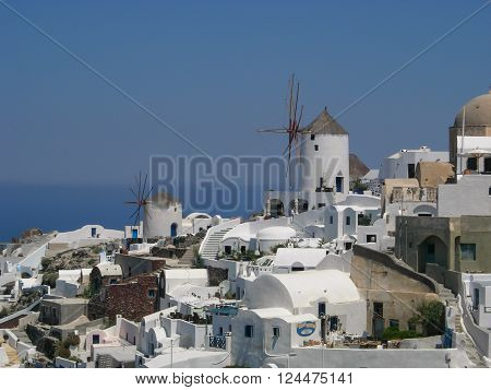 Two old windmills among the whitewashed houses in Santorini Greece