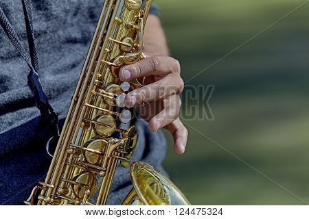 Close up of the hands of a young adult man playing a saxophone