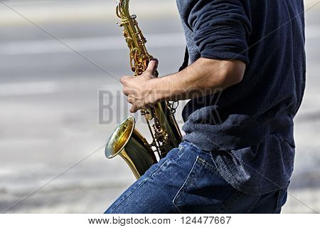 Profile of Young adult man playing a saxophone