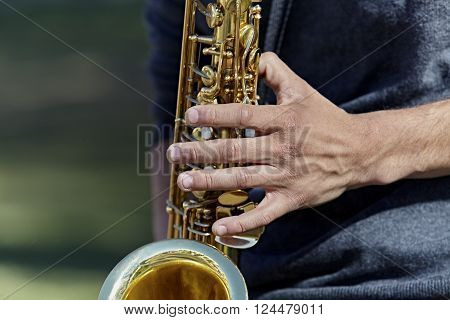 Close up of Young adult man's hands playing a saxophone