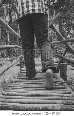 Feet walking over a wooden bridge walkway
