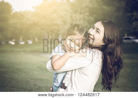 Lifestyle portrait mom and daughter in happines at the outside in the park