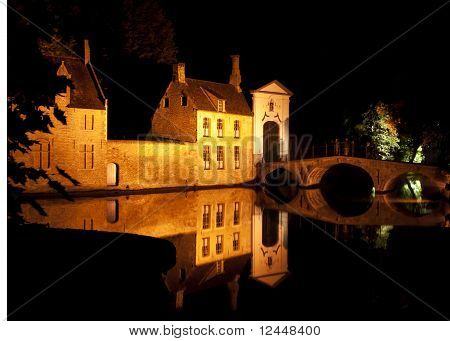The entrance and bridge of Bruges Beguinage during a pitch black night.