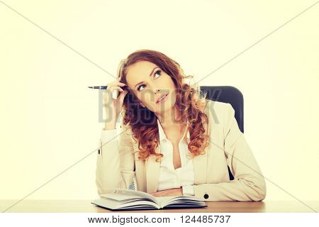 Thoughtful businesswoman by a desk