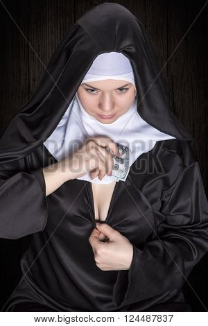 Nun hides a wad of money in his between the breasts view on top