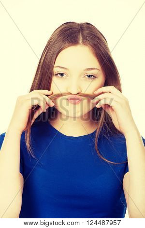 Teenager making moustache from hair.