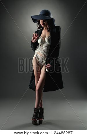 Image of model dressed in sexy lace lingerie, coat and hat