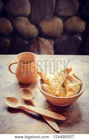 Wooden bowl of freshly baked homemade pastry with jag and spoons on an old barn wood table. Rustic background. Vertical.