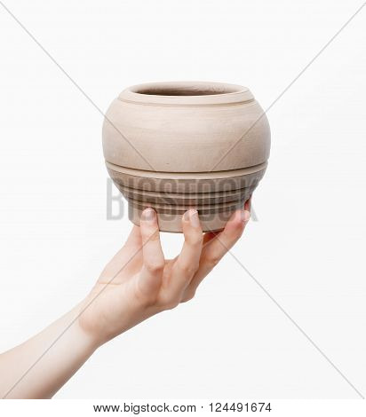 Close view of unburnt clay pot in a woman's hand isolated on white background