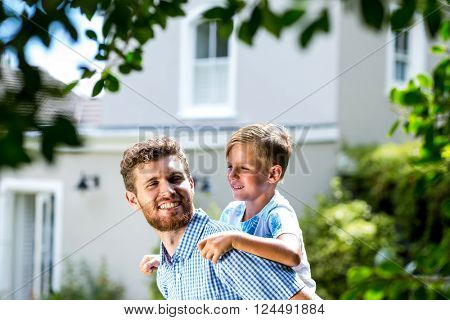 Happy father piggybacking son while standing in yard