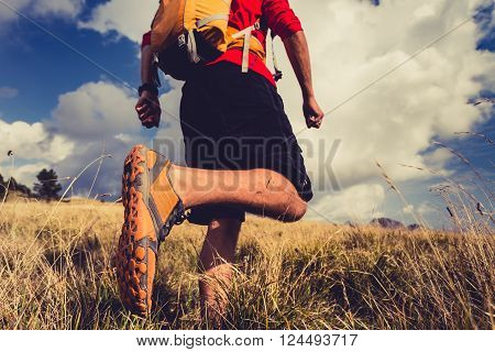 Hiking man or trail runner walking in mountain inspirational landscape. Fitness and healthy lifestyle hiker or trekker walk on dry grass fall autumn nature. Travel in Italy Europe. Selective focus on a sports shoe.