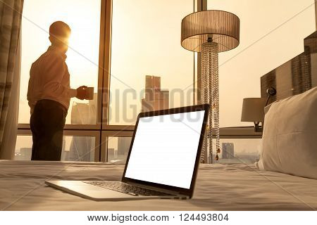 Laptop computer on white bed sheets in cozy room with copy space blank screen. Young businessman with cup of coffee standing at window looking at city scenery on the background