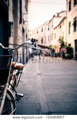 City old bicycle handlebar and basket over blurred street background with people walking. Vintage retro style bike with bokeh copy space.