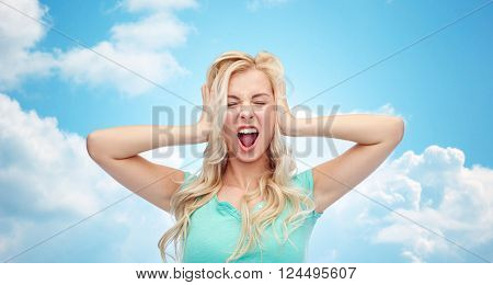 emotions, expressions, stress and people concept - young woman holding to her head and screaming over blue sky and clouds background