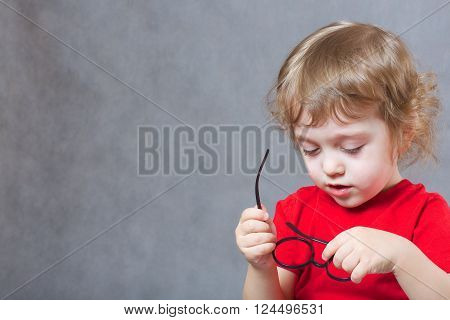 A Boy Of 3 Years Old  Is Putting On Eyeglasses