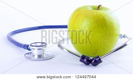 Stethoscope and green apple isolated on white background.