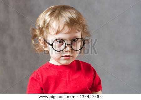 A boy of three years in eye glasses frame without lens.