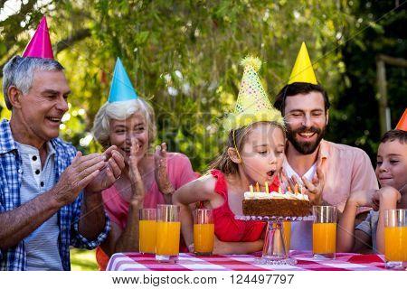 Happy family celebrating birthday at table in yard