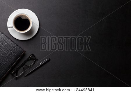 Office leather desk table with coffee cup, notepad and pen. Top view with copy space