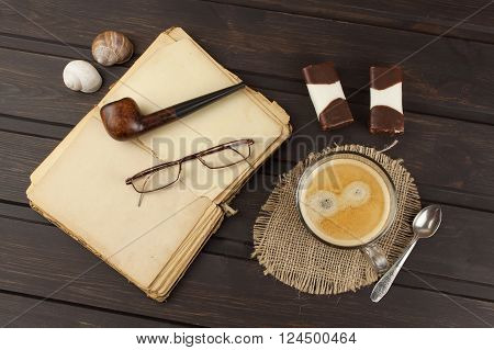 Old books, eyewear and cup of coffee on a dark wooden table. Reading vintage old book and coffee. Relax with a book and a good coffee.