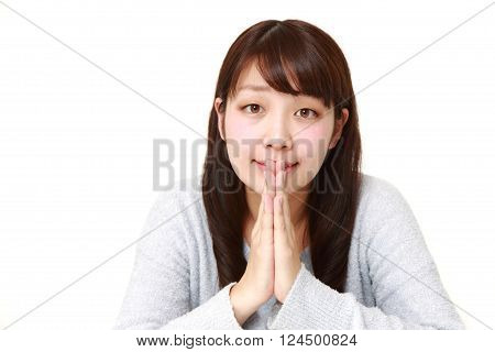 young Japanese woman folding her hands in prayer
