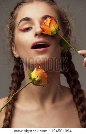 Young beautiful woman with beautiful braids covering her eye by fresh rose